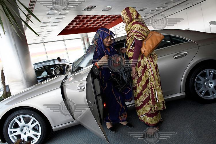 Afaf Osman, 59, and Asha Abdurhim, 47, taking a look at a new Mercedes in the DAL Motor Co showroom. Sales of luxury cars are increasing in Khartoum.