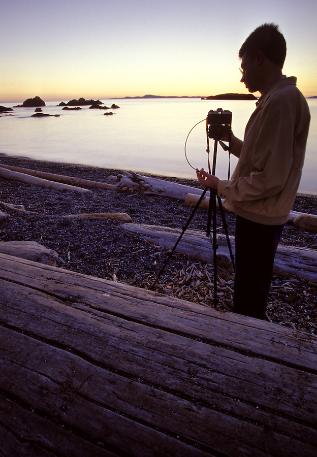Photographer photographing sunset, Deception Pass State Park, Fidalgo Island, Washington