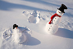 Snowman with red scarf and black top hat standing next baby snowman making snow angel,  snowy meadow  in back ground.