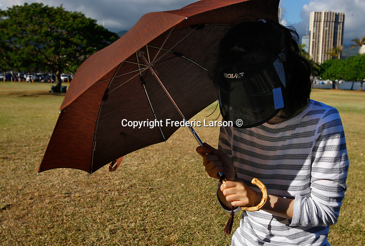 A woman protects herself from the sun on Magic Island in Hawaii.