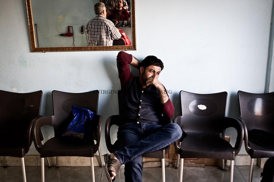 EGYPT, 6 of October City: Abu Ali is in his thoughts while his children area playing around the hairdresser saloon. 28th February 2014<br /> <br /> EGYPTE, 6 Octobre Ville: Abu Ali est dans ses pens&eacute;es tandis que ses enfants jouent autour du salon de coiffure. 28th F&eacute;vrier 2014