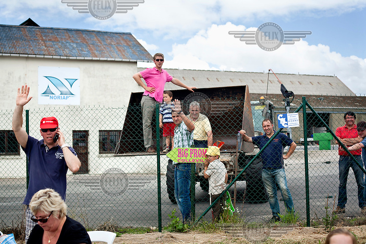 Locals wait on the side of a road including a man and child standing in the lifting fork of a tractor as they wait see the Tour de France cycling competition pass through their village.