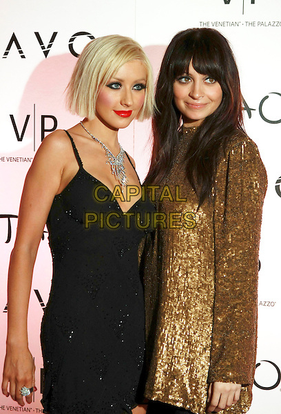 CHRISTINA AGUILERA & NICOLE RICHIE.hosts at Tao at the Venetian and LAVO at the Palazzo Celebrating New Year's Eve in Las Vegas, USA.  .31st December 2009.NYE half length black dress necklace beaded silver red sleeveless cleavage  skinny thin weight loss  gold sequined sequin long sleeved tunic  .CAP/ADM/MJT.© MJT/AdMedia/Capital Pictures.