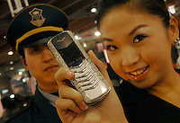An assistant holds-up a Nokia Vertu jewellery phone encrusted with 900 small diamonds worth 200,000 rnb Chinese rnb at the Guangzhou Luxury Goods Fair in China.