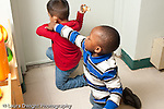 Education preschool 3-4 year olds argument conflict two boys struggle over possesion of toy one boy is holding out of reach of the other boy horizontal