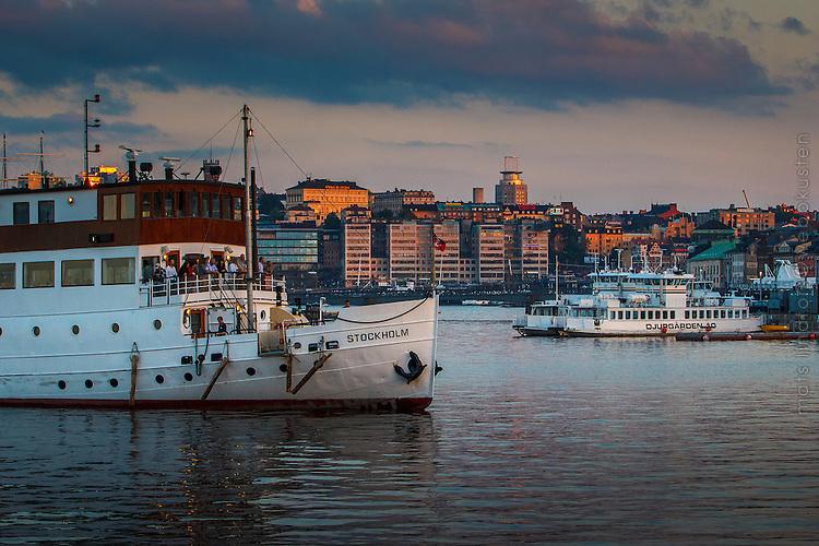 Båt på väg till kajen vid Nybroviken med människor i solnedgång Stockholm