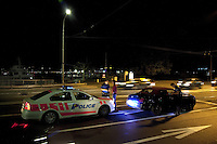 Switzerland. Geneva. Two police officers control at night the identity of a young man from Saudi Arabia. The man was driving his convertible Bentley too fast on the Mont-Blanc bridge and will receive a fine for speed driving. A traffic ticket is a notice issued by a law enforcement official to a motorist accusing violation of traffic laws. Traffic tickets generally come in the form of citing a moving violation, such as exceeding the speed limit. The policeman (R) is wearing a ballistic vest, bulletproof vest or bullet-resistant vest which is an item of personal armor that helps absorb the impact from knives, firearm-fired projectiles and shrapnel from explosions, and is worn on the torso. Soft vests are made from many layers of woven or laminated fibers and can be capable of protecting the wearer from small-caliber handgun and shotgun projectiles. 11.05.12 © 2012 Didier Ruef..