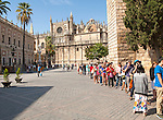 Line of tourists queueing to enter the Alcazar in Seville, Spain with the cathedral in background