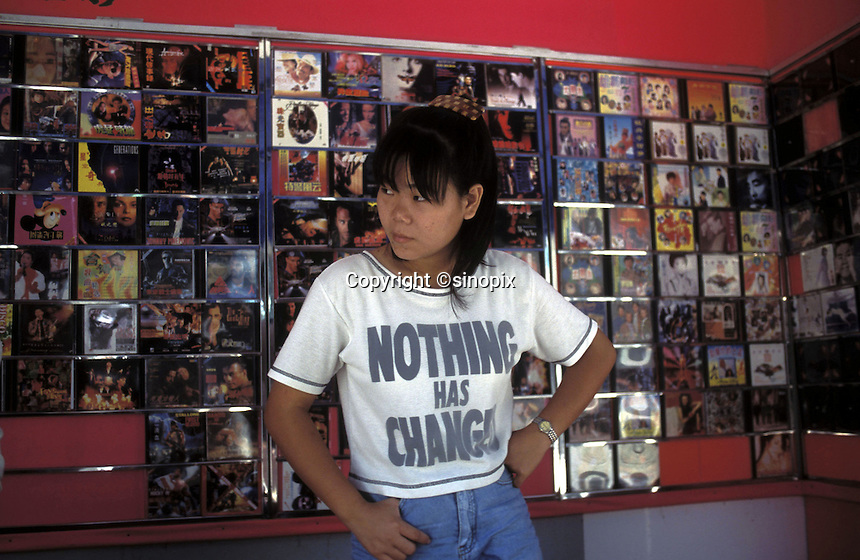 A young woman sells pirated VCDs of western/hollywood films in Shenzhen, China.