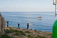 Alcuni immigrati Tunisini salutano l'arrivo di una barca di clandestini che si appresta ad entrare nel porto di Lampedusa. A boat full of Tunisian immigrants arrive on the tiny island of Lampedusa, Italy.