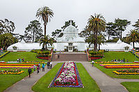 Front view of San Francisco Conservatory of Flowers in Golden Gate Park with tourists and flower beds
