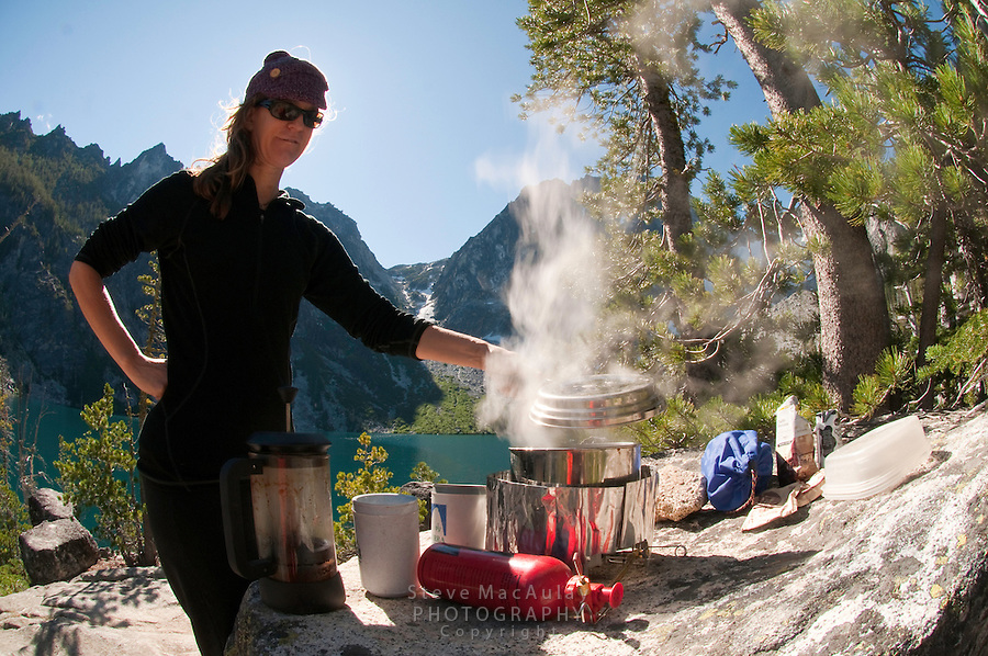 Backpacker checking a pot of boiling water on camp stove at camp on Colchuck Lake, Alpine Lakes Wilderness, WA.