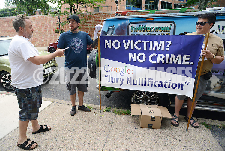 DOYLESTOWN, PA - JULY 08:  An unidentified man is handed a pamphlet by Mike Randazzo, 29, of Media, Pennsylvania and Jeff Peurie of Eddystone, Pennsylvania during a protest for a Bucks County defendant charged with marijuana possession July 8, 2014 in Doylestown, Pennsylvania.  (Photo by William Thomas Cain/Cain Images)