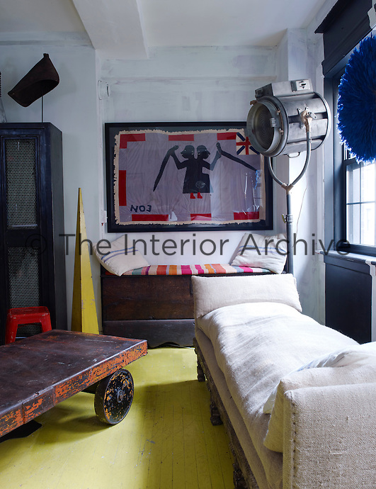 An industrial cart serves as a coffee table in the living area which is furnished with an Italian day bed a 1950s Hollywood stage light and a framed African tribal flag