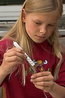 Kinder basteln einen Lichterkranz für die Adventszeit, Adventskranz, Kind wickelt Draht um eine Kerze