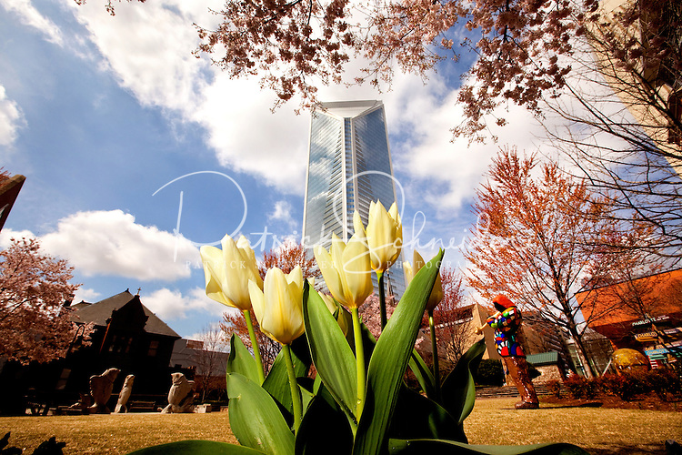 The Duke Energy Headquarters rises high in the background against a city in bloom. Foreground shows The Green in uptown Charlotte.