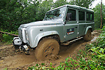 Land Rover Driving Experience Defender TD4 off roading along muddy forest track. Dunsfold Collection of Land Rovers Open Day 2011, Dunsfold, Surrey, UK. --- No releases available, but releases may not be necessary for certain uses. Automotive trademarks are the property of the trademark holder, authorization may be needed for some uses.