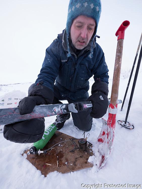 Mann varmer opp skibinding over primus for å få ut is og snø. ---- Man heating ski binding to melt snow.