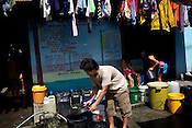 A family collects water to wash clothes outside their house in their Shanty Town, Sitio Aroma in Barangay 105, Manila in Philippines. Photo: Sanjit Das