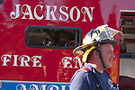 Focus on EMT inside Jackson Wisconsin Ambulance helping a patient with a firefighter outside