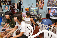 "Thailand. Bangkok. Tha Tian. A group of boys play on PlayStation 3. The PlayStation 3, commonly abbreviated PS3, is the third home video game console produced by Sony Computer Entertainment, and the successor to the PlayStation 2 as part of the PlayStation series. Television and plastic chairs. Pictures of american wrestlers and King Bhumibol are taped on the wall. Bhumibol Adulyadej (born 5 December 1927), is the current King and Head of the State of Thailand. Publicly acclaimed ""the Great"" he is also known as Rama IX. Having reigned since 9 June 1946, he is the world's longest-serving current head of state and the longest-serving monarch in Thai history. Tha Tian is a community located in the downtown area and in the center of the urban historic district, called Koh Rattanakosin. 02.04.09 © 2009 Didier Ruef"