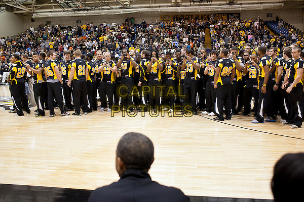 Members of the Townson University football team take pictures of United States President Barack Obama during halftime of the Oregon State vs Towson University basketball game in Towson, Maryland, November 26, 2011. Members of the football team were honored for winning the Colonial Athletic Association regular-season title. .CAP/ADM/CNP/PS.©Pete Souza/White House/CNP/ADM/CapitalPictures