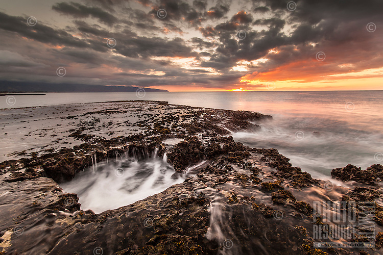Water cascades off of a rocky shelf under a golden sunset at Shark's Cove, North Shore, O'ahu.
