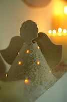 An illuminated Christmas angel made of felt and dusted with fake snow