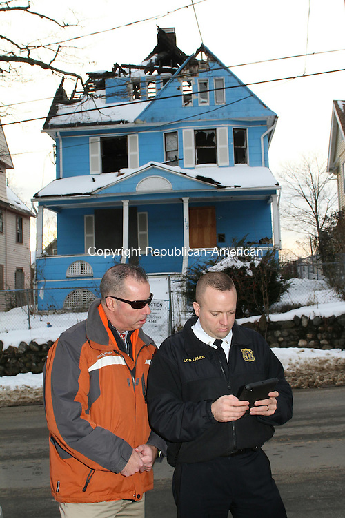 WATERBURY, CT-19 December 2013-121913LW01 - Lt. Daniel Lauer, director of Waterbury's Blight Task Force, right, and Michael Gilmore, the task force's deputy director, inspect a blighted property at 197 Willow St. in Waterbury. The home is next on the city's lilst for demolition and should be gone in about six weeks, Lauer said. It burned a year and a half ago and the owner walked away after realizing his insurance had lapsed and he didn't have the money to fix it, Lauer said. The city tried to sell it at a tax auction, but there were no takers. <br />