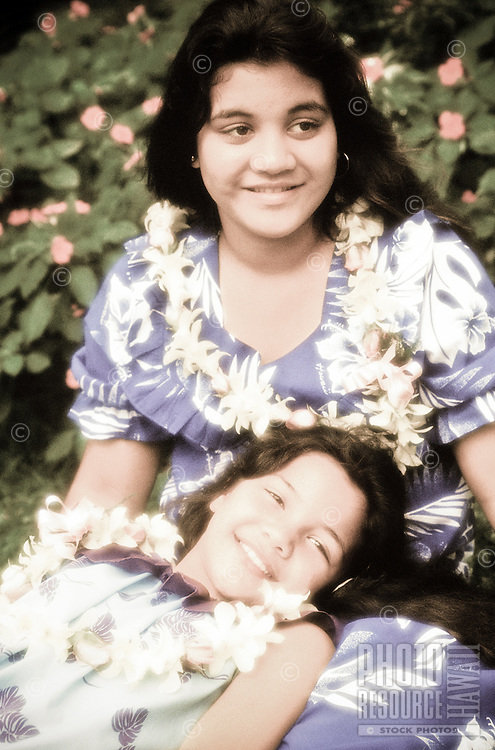 Two young girls wearing leis and muumuus