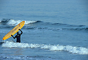 Surfers riding the waves at  New Hampshire 's seacoast, which is part of the New England USA seacoast