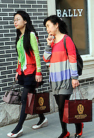 Chinese women carrying shopping bags past a Bally store at Beijing Scitech Premium Outlet Mall in Beijing, China. Opened in July 2009, Beijing Scitech Premium Outlet Mall is located in Beijing's most prestigious villa neighborhood. The outlet, featuring Colonial and Victorian architecture, the first of its kind in China, contains gallery of top-tier luxury brands, as well as showcases a wide selection of popular sports and leisure brands at discounted prices..15 May 2010