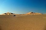 Africa, Algeria, Sahara Desert. Speeding Series 2a Land Rover 88 over a sandy plain contrasting against the scenic sand dunes of the Sahara Desert. --- No releases available, but release may not be required. Automotive trademarks are the property of the trademark holder, authorization may be needed for some uses.
