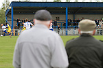 Vauxhall Motors FC 0 Solihull Moors 2, 26/04/2014. Rivacre Park, Conference North. Two spectators in caps watching the first-half action during Vauxhall Motors (in white) play Solihull Moors at Rivacre Park in the final Conference North fixture of the season. It was to be the last match for the Ellesmere Port-based home club, named after the giant car factory in the town, who have resigned from the professional pyramid system to return to local amateur football due to spiralling costs and low attendances. Their final match resulted in a 2-0 home defeat, watched by a crowd of only 215. Photo by Colin McPherson.