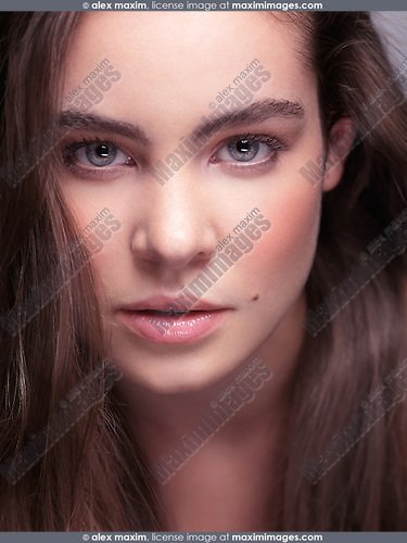 Beautiful young woman face with natural makeup and gray eyes