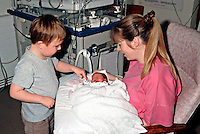 Premature infant in an high dependency intensive care cot in a special care baby unit being held for the first time by her mother and her older brother. ..© SHOUT. THIS PICTURE MUST ONLY BE USED TO ILLUSTRATE THE EMERGENCY SERVICES IN A POSITIVE MANNER. CONTACT JOHN CALLAN. Exact date unknown.john@shoutpictures.com.www.shoutpictures.com.
