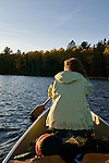 A woman paddles a canoe on Galerairy lake in Ontario's Algonquin National Park in Canada.