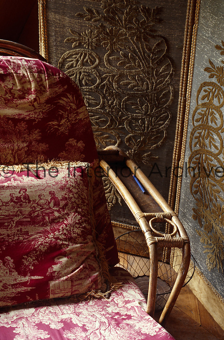 An antique bamboo sun-lounger upholstered in toile de Jouy sits next to an !8th century screen