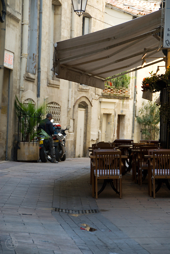 A man mounts a motorcycle near a cafe with oudoor seating under an awning on a traditional street in the old city, Montpellier, Southern France, October 7 2008