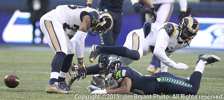 Seattle Seahawks wide receiver Tyler Lockett (16) has the ball ripped away by St. Louis Rams cornerback Janoris Jenkins (21) after catching a pass over the middle at CenturyLink Field in Seattle, Washington on December 27, 2015.  Rams safety mark Barron (26) looks for the fumble. The Rams beat the Seahawks 23-17.      ©2015. Jim Bryant Photo. All Rights Reserved