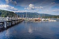 Boats moored at jetty with mountains in the background. Deep Cove, Burrard Inlet, Vancouver, British Columbia, Canada.