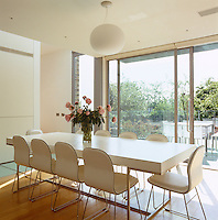 The dining room, which opens out onto a balcony, is furnished with a B&B Italia dining table and leather dining chairs by Jasper Morrison