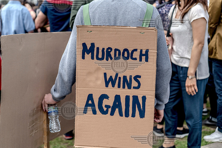 A man with a placard that reads: 'Murdoch wins again' during a pro EU demonstration in Parliament Square on the morning after the EU reeferendum.