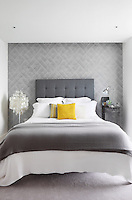 A bedroom with a grey patterned wallcovering. A floor lamp with hanging discs stands beside a double bed with an upholstered headboard. A bright splash of a yellow cushion provides a vibrant contrast to the grey hues.