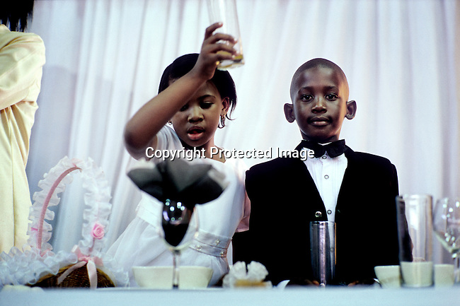 SOWETO, SOUTH AFRICA MARCH 12: Unidentified children join a toast while attending a wedding reception on March 12, 2005 in Soweto, Johannesburg, South Africa. A couple celebrated a white wedding in a rented hall. Soweto is South Africa?s largest township and it was founded about one hundred years to make housing available for black people south west of downtown Johannesburg. The estimated population is between 2-3 million. Many key events during the Apartheid struggle unfolded here, and the most known is the student uprisings in June 1976, where thousands of students took to the streets to protest after being forced to study the Afrikaans language at school. Soweto today is a mix of old housing and newly constructed townhouses. A new hungry black middle-class is growing steadily. Most residents work in Johannesburg but the last years many shopping malls has been built, and people are starting to spend their money in Soweto. (Photo by Per-Anders Pettersson)