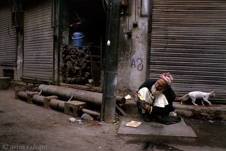 On a cold winter morning in the old city of Lahore, a traveling day laborer prepares a fire in a portable stove to help keep him warm