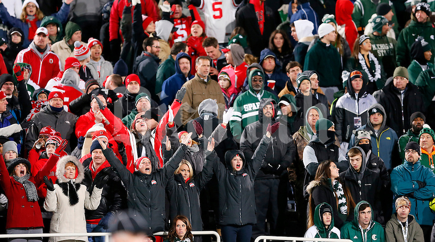 Happy Buckeye fans cheer after a touchdown by running back Dontre Wilson (2) as Spartan fans show their dejection during Ohio State's 49-37 win over Michigan State in the NCAA football game at Spartan Stadium in East Lansing, Michigan on Nov. 8, 2014. (Adam Cairns / The Columbus Dispatch)