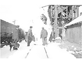 A snow-covered D&amp;RGW locomotive, number and class obscured for obvious reasons, receives a dusting to uncover its headlight for the trip ahead while the crew watches at the Chama coaling tower.<br /> D&amp;RGW  Chama, NM