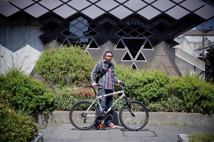 Tokyo, April 20 2011 -.(eng )Yoshiyuki Sakamoto, 38, is pictured with his bicycle in front of the Tokyo Budokan, shelter for earthquake and nuclear refugees..Yoshiyuki lost his job as a milk delivery man in Iwaki, a few days after the quake. Without income and electricty in his house, pushed by the fear of radioactivity, he rode his bike  to Tokyo, 350km away, for a 15 hours journey..4 days later, when the shelter is closed, he will be back to Iwaki, by bike..Yoshiyuki doesn't want to go back but cannot afford everyday fees in a public housing unit...(fr) Yoshiyuki Sakamoto, 38 ans, pose avec son vélo devant le Tokyo Budokan, centre d'accueil pour réfugiés du seisme et de la centrale de Fukushima. Yoshiyuki a perdu son emploi de livreur de lait a Iwaki quelques jours après le tsunami. Sans revenu, sans electricte chez lui, pousse par la peur de la radioactivite, il a fui vers Tokyo en vélo, parcourant les 350km en 15h avant d'arrriver au Tokyo Budokan. Quatre jours plus tard, quand le centre fermera, il repartira vers le nord, contre son gré. Il espère y retrouver son emploi. Sans économies ni allocation chomage, il n'a pas souhaité postuler pour un HLM de la ville de Tokyo ou pour un place à l'hotel puisqu'il n'a pas les moyens de payer les dépenses courantes.