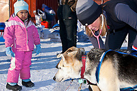 Four year old Anita Jemewouk of Elim watches veterinarian Emi Berger of New York examine a Colleen Robertia dog at the Elim checkpoint during the 2010 Iditarod